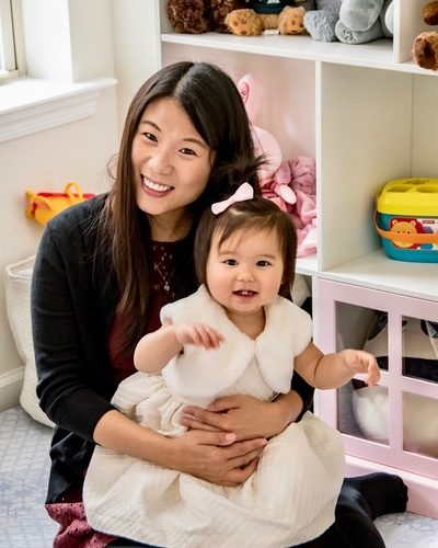 Yinan sits in a child's playroom with her young daughter, who is wearing a white dress.