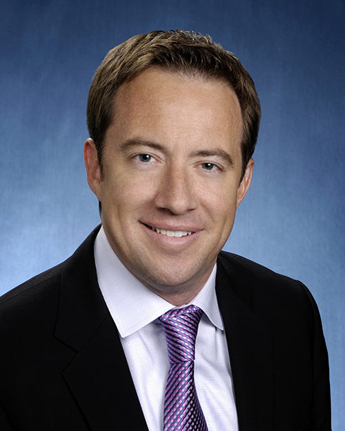 A man in business attire looks into the camera and poses for a headshot.