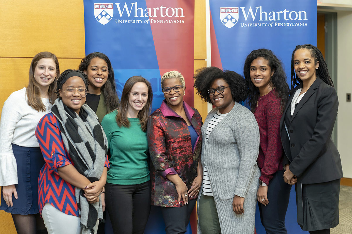 Eight women pose in front of a banner with the Wharton logo.
