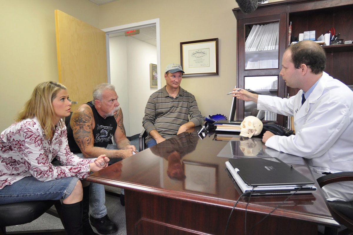 Three people meeting with a doctor in an office.