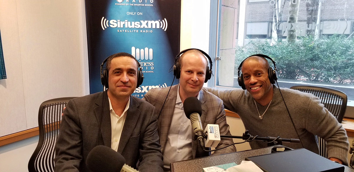 Three men in a radio studio look into the camera and smile for a group photo.