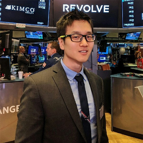 A man with glasses in a suit with New York Stock Exchange screens behind him Exchange