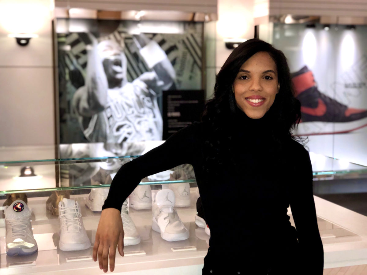 A woman looks at the camera as she poses for a photo in front of a class case of Air Jordan shoes in a Nike store.