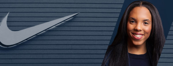 A gray wall with a gray nike logo framing Kerhyl's headshot. She has dark hair and wears a black shirt.