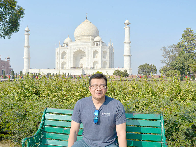 Man poses for a photo in front of the Taj Mahal in Uttar Pradesh, India.