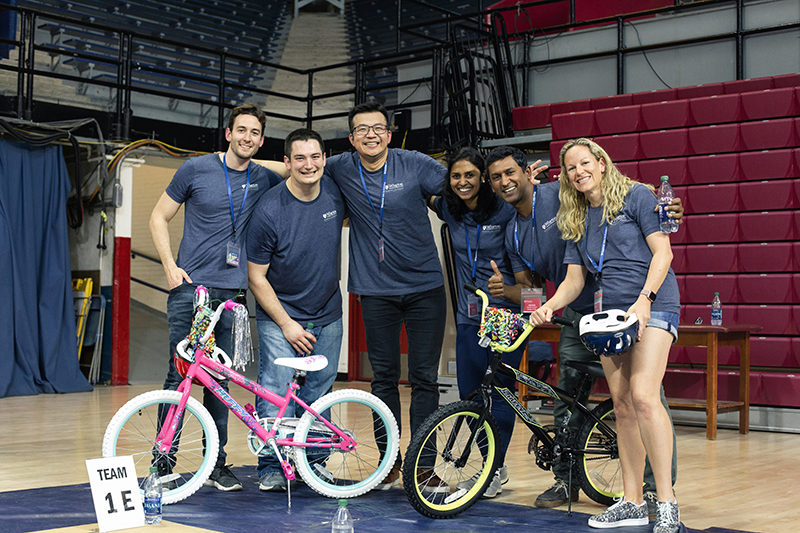 A group of men and women pose for a photo in front of two bicycles at a charity event in a gym.
