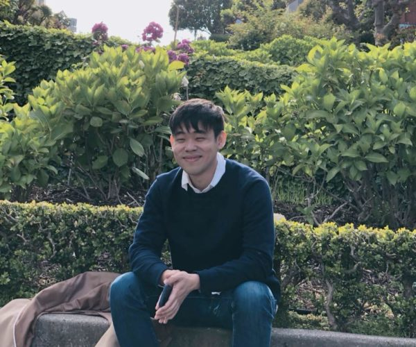 yun cha sitting on a curb outdoors, surrounded by green plants, wearing jeans and a navy blue sweater