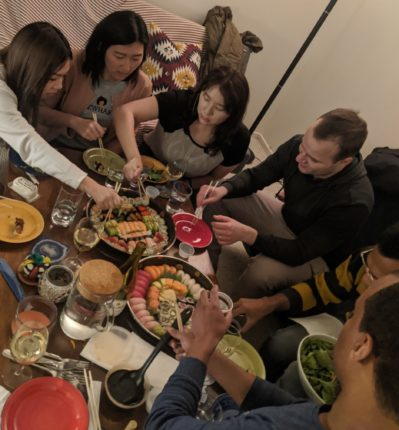 A group of six students in their mid-twenties (three women and three men) share sushi around a coffee table