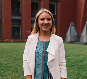 becca bean wearing a teal top and a white jacket on wharton's campus