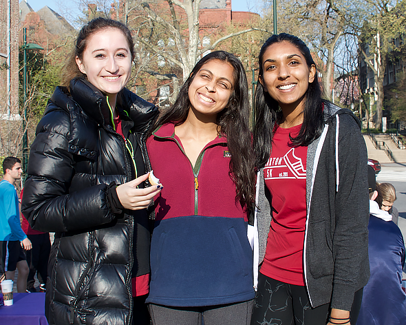 Three students smile outside. Tanu wears a red Wharton 5K shirt.