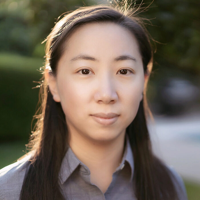 Lin smiles in a headshot. She has long, straight dark hair and wears a purple button-up blouse.