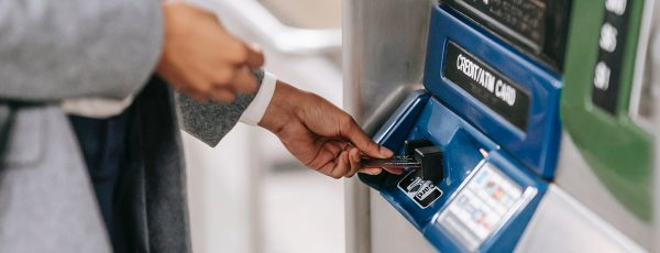 woman inserting card into metrocard machine hero