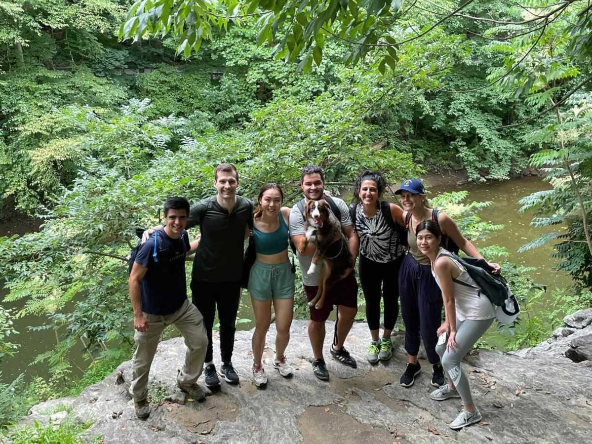 Group of MBA students posing for a photo in a forest
