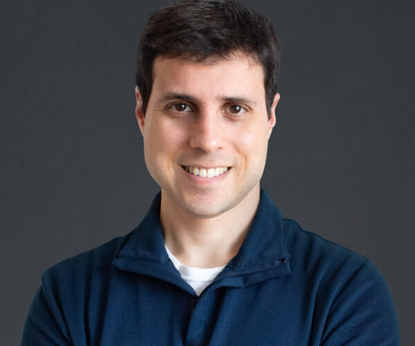 headshot of michael brown, wearing a navy blue long sleeve collared shirt and standing in front of a dark grey backdrop