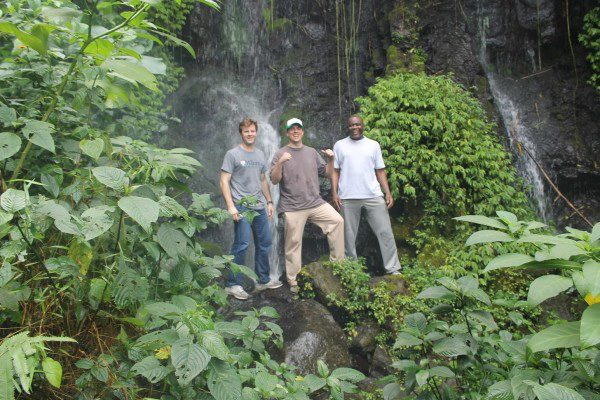 Aris, Ben, and Greg at Mount Cameroon in lush greenery in front of a waterfall