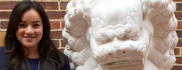 Corinne Low stands in front of a brick wall, next to a white lion statue.